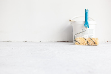 Verf emmer met roller borstel op een witte achtergrond.