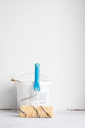 roller brush: Paint bucket with roller brush on white background.