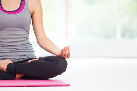 Jonge mooie vrouw doet yoga binnenshuis.