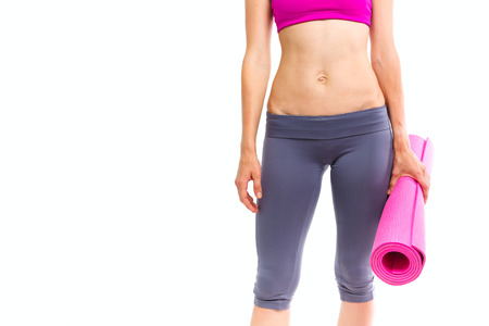 Portait of young beautiful woman holding yoga mat - isolated on white.