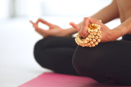 Young beautiful woman meditating in lotus pose.