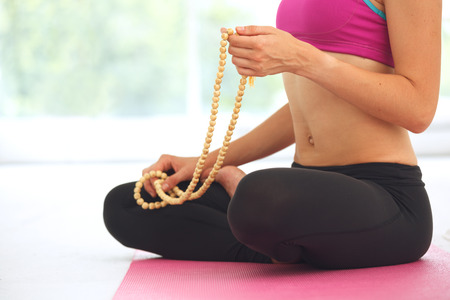 breathing exercise: Young beautiful woman meditating in lotus pose.