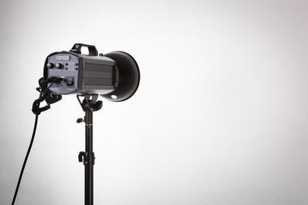 Professional photo studio strobe with reflector on tripod.