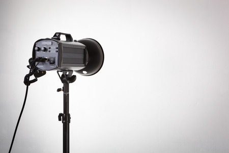 strobe: Professional photo studio strobe with reflector on tripod.