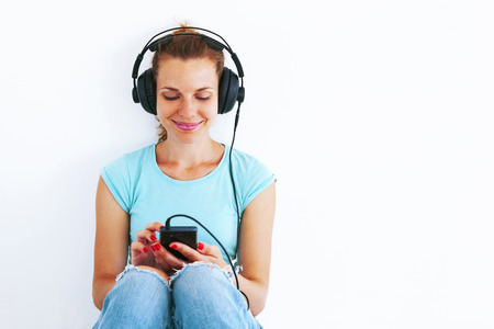 Young woman in casual dress listening music with headphones. photo