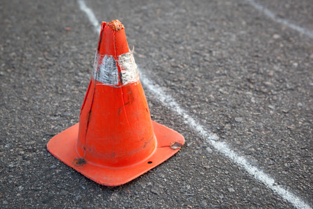 road safety: Old orange striped cone on road - driving school concept image.
