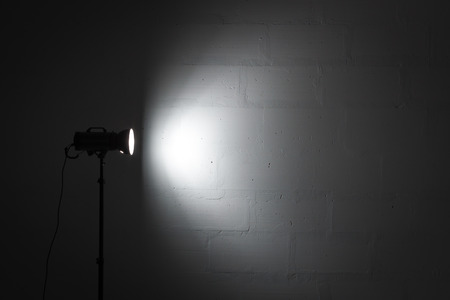 reflector: Professional photo studio strobe with reflector on tripod.