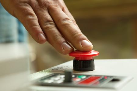empujando: Hombre mano presionando el botón rojo de parada de emergencia.