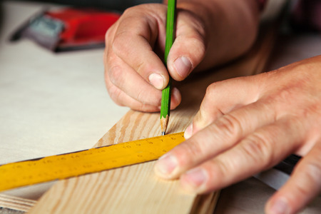 proffesional: Male hands with ruler and pencil closeup. Proffesional carpenter at work. Stock Photo