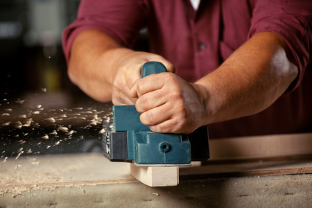 maker: Carpenter working with electric planer on wooden plank in workshop. Stock Photo