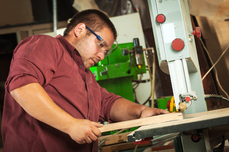 scobs: Professional carpenter working with sawing machine in workshop