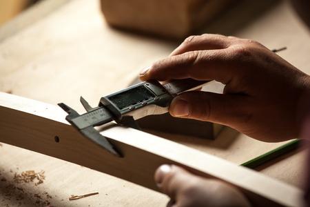 menuisier: Carpenter mesure chaise partie avec étriers électriques dans l'atelier.