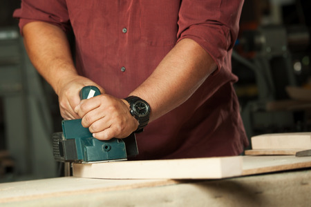 scobs: Carpenter working with electric planer on wooden plank in workshop. Stock Photo