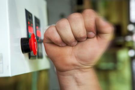 Mão masculina que empurra a tecla de paragem de emergência vermelho. Imagens