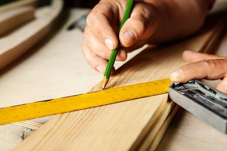 carpintero: Manos masculinas con regla y lápiz de cerca. Carpintero profesional en el trabajo.