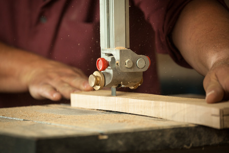 scobs: Professional carpenter working with sawing machine in workshop - closeup. Stock Photo