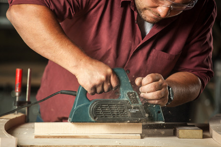 tool: Carpenter arbeitet mit elektrischer Hobel auf Holzbrett in der Werkstatt. Lizenzfreie Bilder