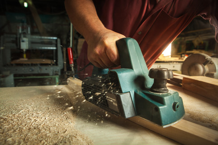 carpentry: Carpenter working with electric planer on wooden plank in workshop. Stock Photo