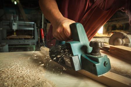 Carpinteiro que trabalha com a plaina elétrica na prancha de madeira na oficina.