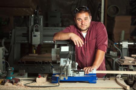 Portret van gelukkige professionele timmerman op zijn werkplek. Stockfoto