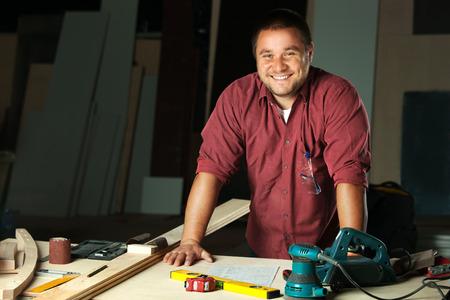 carpintero: Retrato de carpintero profesional feliz en su lugar de trabajo.
