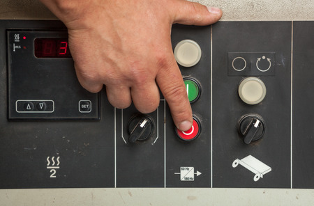 red button: Male hand pushing red stop button closeup. Stock Photo