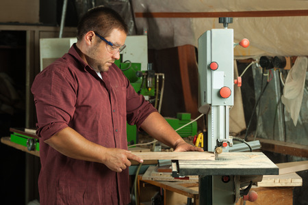 woodworker: Professional carpenter working with sawing machine in workshop. Stock Photo