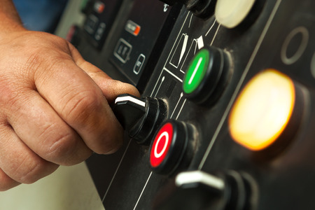 control panel: Male hand operating switches and buttons on control panel. Stock Photo