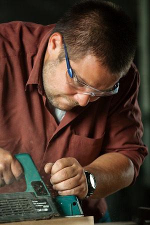 planer: Carpenter working with electric planer on wooden plank in workshop. Stock Photo