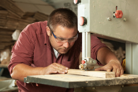 Professional carpenter working with sawing machine in workshop. 스톡 콘텐츠