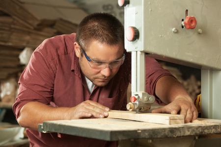 carpintero: Carpintero profesional que trabaja con el aserrado máquina en el taller.