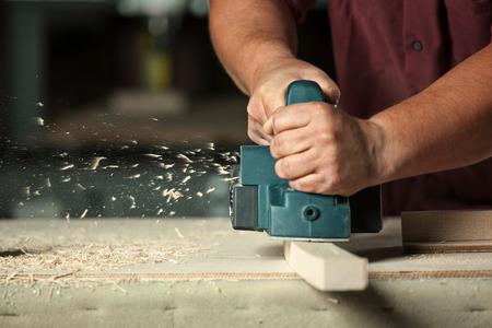 menuisier: Carpenter travailler avec rabot électrique sur planche de bois dans l'atelier.