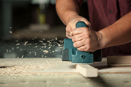 carpenter's sawdust: Carpenter working with electric planer on wooden plank in workshop. Stock Photo