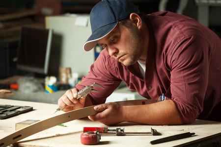 carpintero: Carpintero de medici�n parte silla con pinzas el�ctricas en taller. Foto de archivo