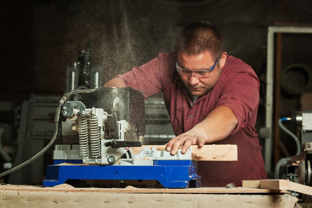 scobs: Professional carpenter working with sawing machine in workshop. Stock Photo