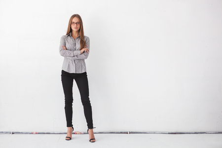person standing: Portrait of young beautiful business woman standing against white wall.