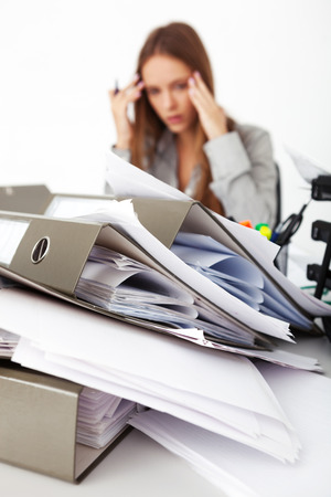 paperwork: Portrait of young beautiful business woman surrounded by big pile of documents. Stock Photo