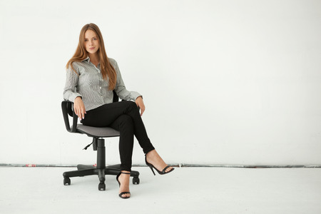 full: Portrait of young beautiful business woman sitting on chair against white wall.