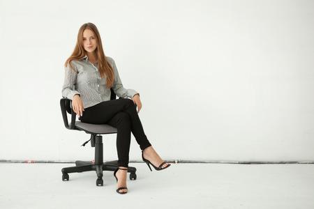 completo: Retrato de joven bella mujer de negocios sentado en la silla contra la pared blanca.