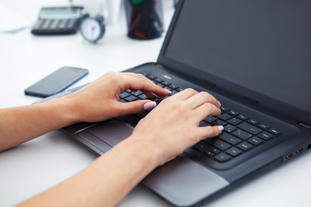 This is Closeup of woman hands working with laptop. Stock Photo