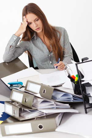 Portrait of young beautiful business woman surrounded by big pile of documents. Stock Photo