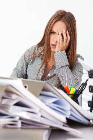 beautiful businesswoman: Portrait of young beautiful business woman surrounded by big pile of documents. Stock Photo