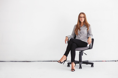 leaning against: Portrait of young beautiful business woman sitting on chair against white wall.