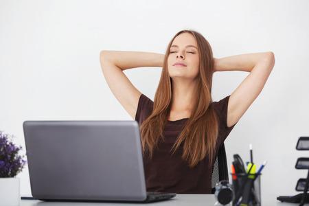 Portret van jonge mooie vrouw ontspannen op kantoor.