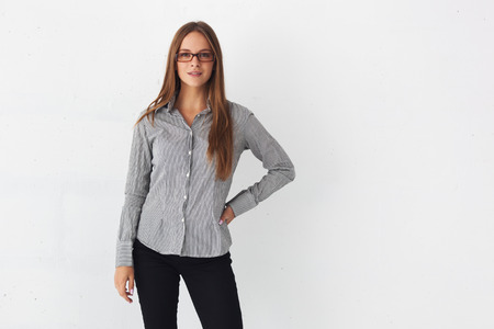 casual office: Portrait of young beautiful business woman standing against white wall.
