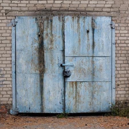 door: This is old weathered painted garage doors.