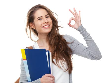 흰색 배경에 고립 된 확인 기호를 게재하는 젊은 행복 한 학생. 스톡 콘텐츠