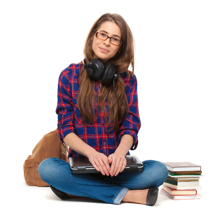 Portrait of happy female student sitting isolated on white.