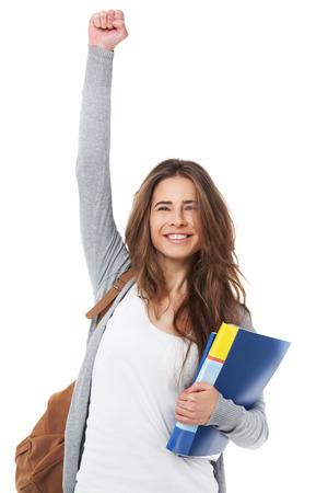 Opgewonden vrouwelijke student verhoging van de hand haar hand op een witte achtergrond.
