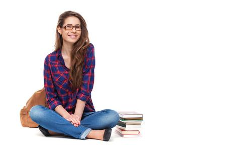 Portret van gelukkige vrouwelijke student zitten geïsoleerd op wit.